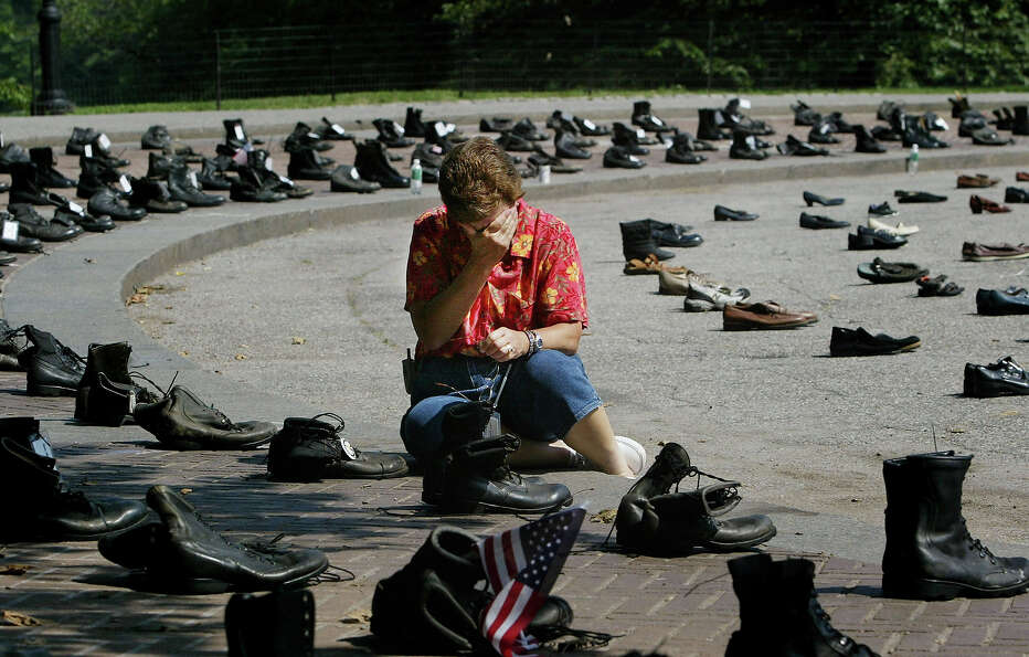 Sue Niederer of Pennington, New Jersey grieves over a memorial representing her son, Seth Dvorin, wh