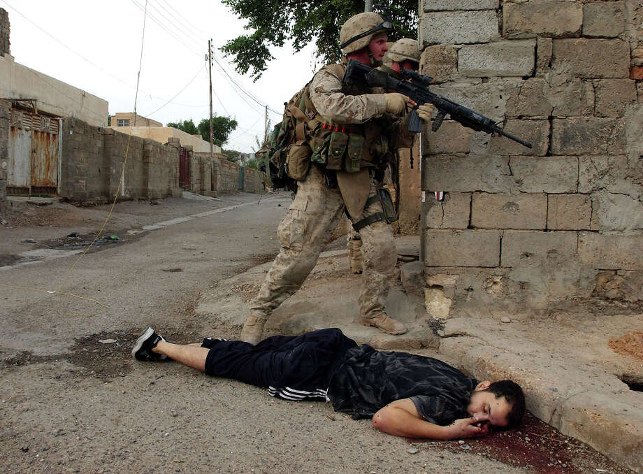 U.S. Marines from the 1st U.S. Marines Expeditionary Force, 1st Battalion, 3rd Marines Regiment, Bravo Company pass by a dead body of a suspected insurgent during the ground offensive November 9, 2004 in Fallujah, Iraq. U.S. troops moved into the center of Fallujah searching homes and using loudspeakers to try to bring the militants out onto the streets. Photo: Marco Di Lauro, Getty Images / 2004 Getty Images