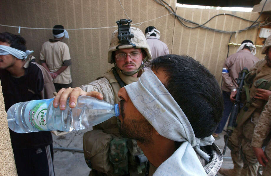 A U.S. Marine from the 1st U.S. Marines Expeditionary Force, 1st Battalion, 3rd Marines Regiment, Bravo Company, gives some drinking water to an arrested Iraqi man November 13, 2004 in Fallujah, Iraq. According to Iraqi National Security Adviser Kasim Dawood, 1000 insurgents have been killed and 200 insurgents have been captured during the six-day battle. U.S. Marines have been arresting males between the combat age of 15 and 55-years-old. Photo: Marco Di Lauro, Getty Images / 2004 Getty Images