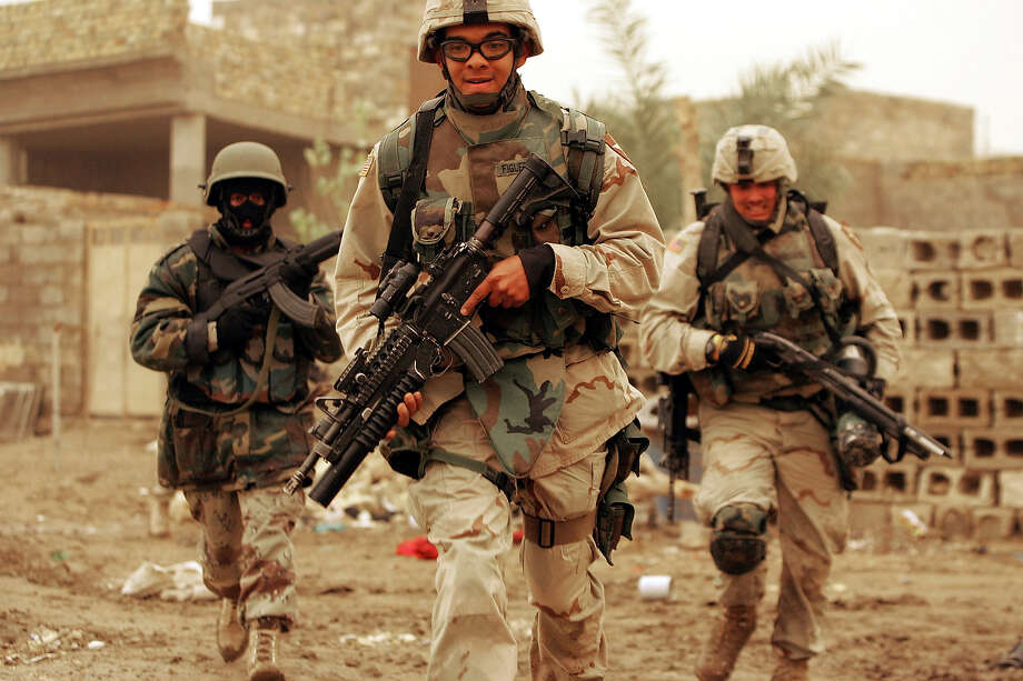 U.S. Army soldiers of the 1st Battalion, 503rd Infantry Regiment and an Iraqi commando run for cover as they conduct a joint patrol searching for insurgents January 24, 2005 in Ramadi, Iraq. The U.S. military is trying to stabilize the city so people can vote safely on January 30. Photo: Joe Raedle, Getty Images / 2005 Getty Images