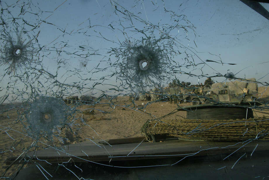 Bullet holes riddle the windshield of a U.S. Marine humvee from Task Force Tarawa March 23, 2003 in the southern Iraqi city of Nasiriyah. The Marines suffered a number of deaths and casualties during gun battles throughout the city. Photo: Joe Raedle, Getty Images / 2003 Getty Images
