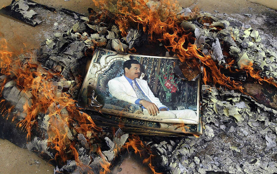 A picture of Saddam Hussein is buned by U.S. Marines April 7, 2003 in Qal'at Sukkar, Iraq. The 24th Marine Expeditionary Unit entered the town looking for weapons and destroying pictures of Saddam Hussein. Photo: Chris Hondros, Getty Images / 2003 Getty Images