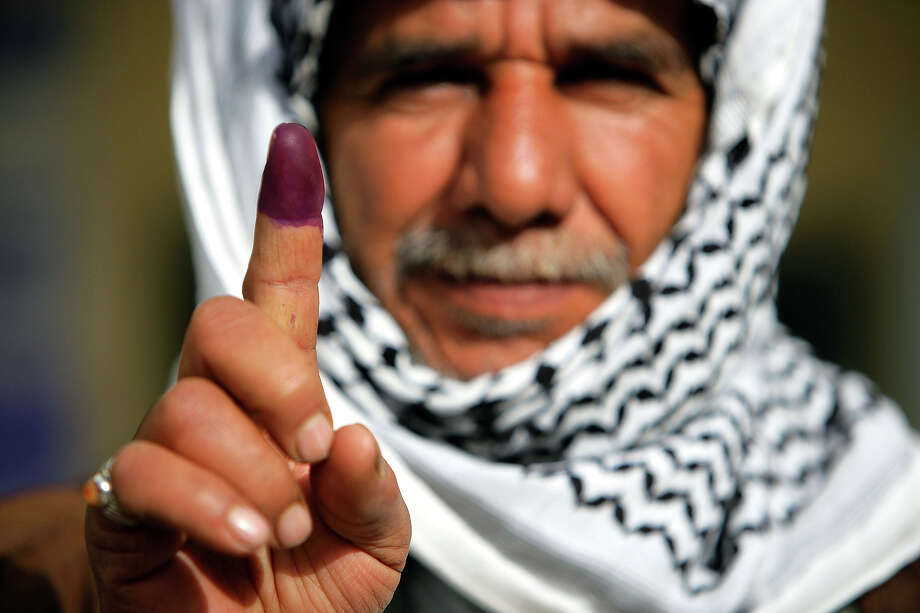 An Iraqi man in Najaf displays his finger to the camera on January 30, 2005 in Najaf, Iraq. The purple dye indicates that he has just voted in Iraq's first elections.  The Shiite holy city of Najaf enjoyed a calm election day with no violence and a good voter turnout reported at many voting stations. Najaf is an important holy city in the Shiite religion and the city has been secured against election violence. Photo: Brent Stirton, Getty Images / 2005 Getty Images