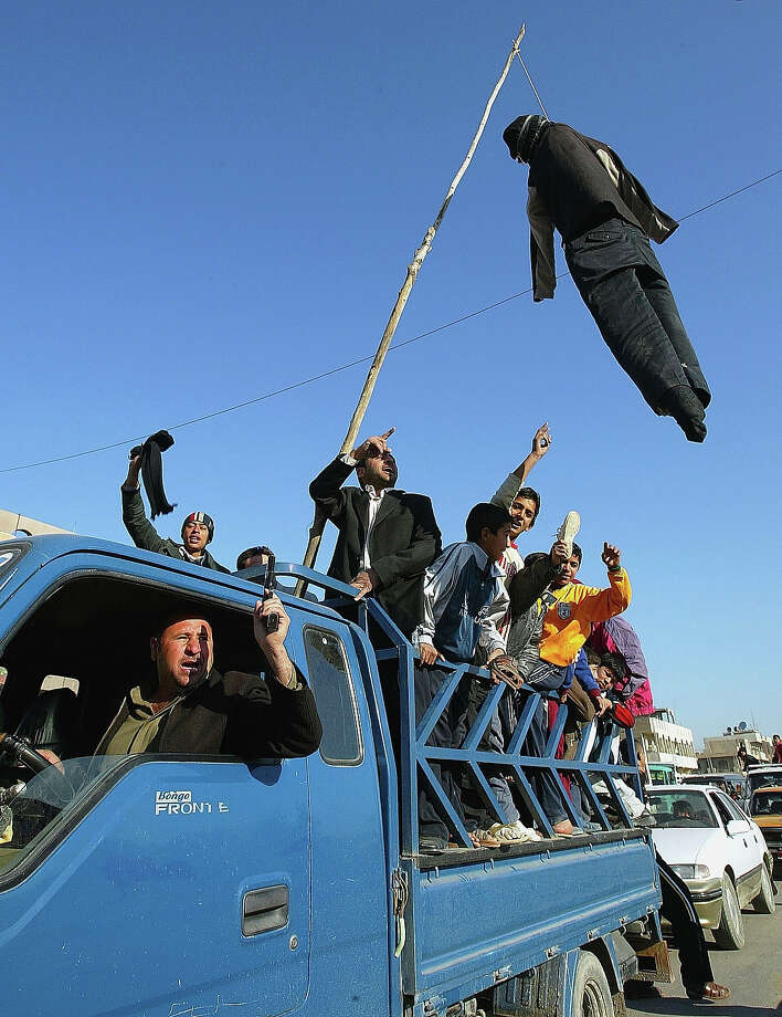 After hearing news about the execution of the former Iraqi president Saddam Hussein, Iraqi's drive through the streets of Sadr City with an effigy of the executed dictator hanging from a rope on December 30, 2006 in Baghdad, Iraq. The former Iraqi president was executed by hanging at 0600 (0300 GMT) in a secure facility in the Northern Baghdad suburb of Khadimeya. Photo: Wathiq Khuzaie, Getty Images / 2006 Getty Images