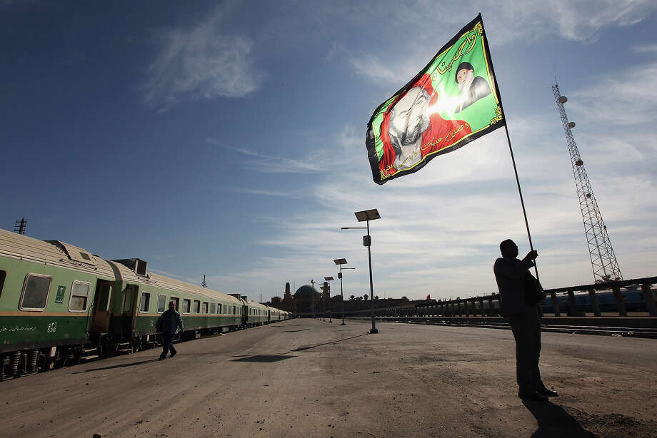 Station master Jawad Khathem prepares to mount a Shi'ite flag on a pole at Baghdad Central Railway Station in preparation for the festival Ashura on December 5, 2011 in Baghdad, Iraq. Photo: Mario Tama, Getty Images / 2011 Getty Images