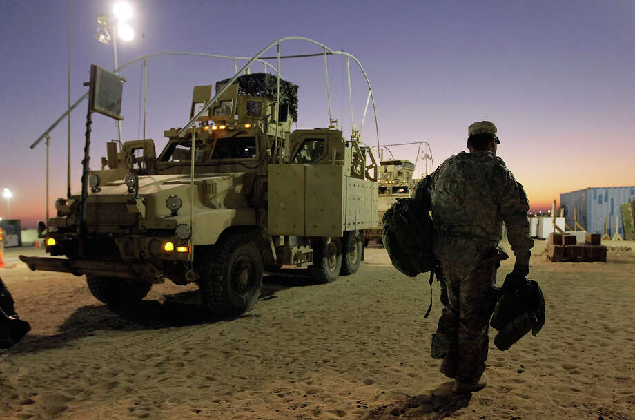 A U.S. Army soldier from the 2-82 Field Artillery, 3rd Brigade, 1st Cavalry Division, carries his gear after arriving in Kuwait from Camp Adder in Iraq on December 7, 2011 at Camp Virginia, near Kuwait City, Kuwait. After seven months in Iraq, the 3rd Brigade has pulled out of the country as part of America's military exodus by the end of December after eight years of war and occupation which included the overthrow of Saddam Hussein. Photo: Joe Raedle, Getty Images / 2011 Getty Images