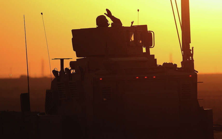 A soldier in the last American military convoy to depart Iraq, from the 3rd Brigade, 1st Cavalry Division, waves after crossing over the border into Kuwait on December 18, 2011 in Khabari Al Awazeem, Kuwait. Around 500 troops from the 3rd Brigade, 1st Cavalry Division ended their presence on Camp Adder, the last remaining American base, and departed in the final American military convoy out of Iraq, arriving into Kuwait in the early morning hours of December 18, 2011. Photo: Mario Tama, Getty Images / 2011 Getty Images