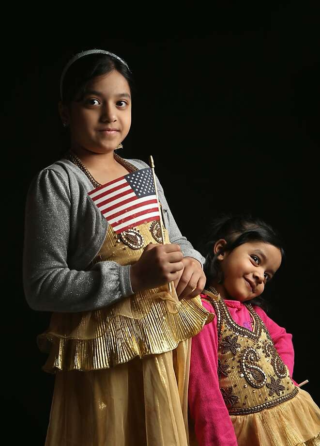 NEW YORK, NY - FEBRUARY 19:  Second grade student Maria Rahman, 7, born in Bangladesh, holds a flag given to her by the U.S. Citizenship and Immigration Services (USCIS), while waiting to receive her citizenship certificate on February 19, 2013 in New York City. Her younger sister Mayisah Rahman, 3, (R), was born in the United States. Her father, Mizanur Rahman, a taxi driver, is a naturalized American from Bangladesh, and their family lives in the Bronx, New York City. Almost 300 foreign-born children of naturalized Americans received citizenship certificates Tuesday at the USCIS center during the special event. Children of naturalized immigrants receive U.S. citizenship if they arrive to the United States as minors, but they must go through a process at USCIS to receive official citizenship documents proving they have become Americans.  (Photo by John Moore/Getty Images) Photo: John Moore, Getty Images