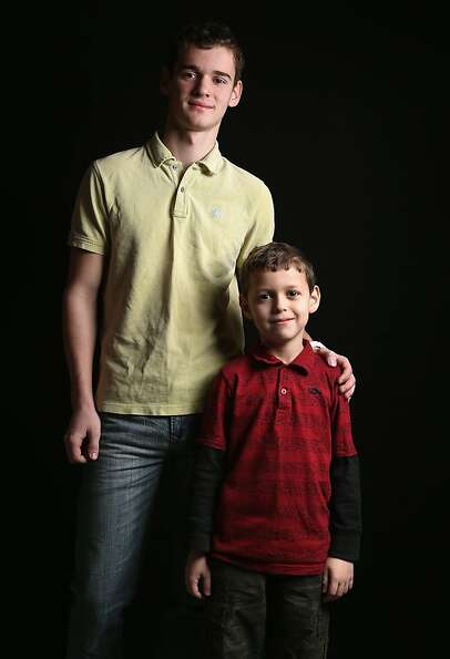 High school senior Denis Dikarev, 17, stands with his third grade brother Timothy Dikarev, 8, while