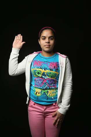 Junilsa Vasquez, 14, from the Dominican Republic, prepares to take her oath of allegiance to the United States at the U.S. Citizenship and Immigration Services (USCIS), office on February 19, 2013 in New York City. She lives in the Bronx, New York with her mother Maria Arias, who works in a restaurant. Photo: John Moore, Getty Images