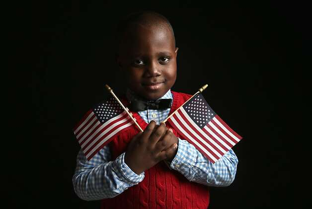 Ifeozuwa Oyaniyi, 5, born in Nigeria, holds flags given to him by the U.S. Citizenship and Immigration Services (USCIS), while waiting to receive his citizenship certificate on February 19, 2013 in New York City. His father, Oluwaseyi Oyaniyi, is a housing inspector, and their family lives in the Bronx, New York City. Photo: John Moore, Getty Images