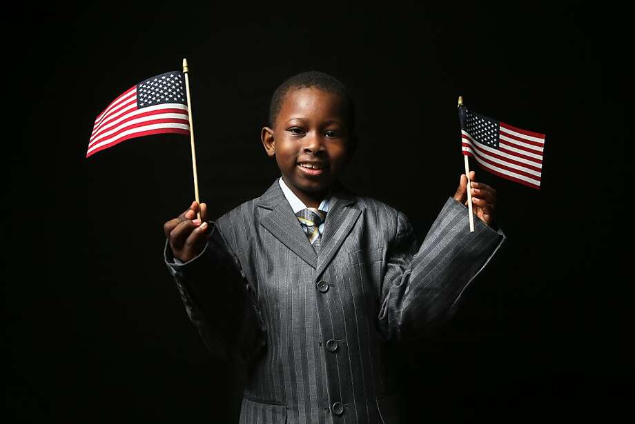 First grader Moussa Doucovre, 6, born in Senegal, waves flags given to him by the U.S. Citizenship and Immigration Services (USCIS), while waiting to receive his citizenship certificate on February 19, 2013 in New York City. His father, a naturalized American citizen, works in retail in the Bronx, New York City. Photo: John Moore, Getty Images