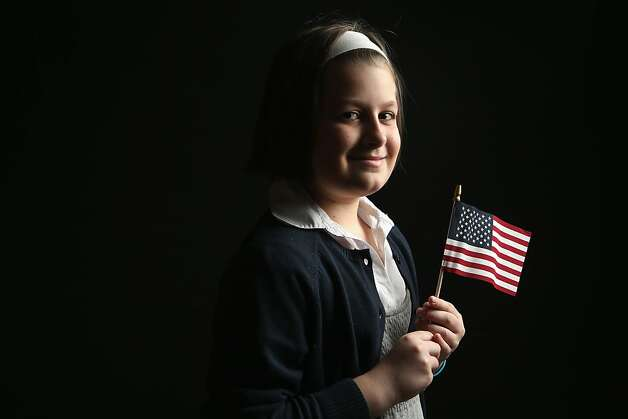 Fourth grade student Ewelina Zdancewicz, 9, born in Poland, holds a flag given to her by the U.S. Citizenship and Immigration Services (USCIS), while waiting for her citizenship certificate on February 19, 2013 in New York City. Her father, a naturalized American from Poland, is an apartment maintenance worker, and their family lives in Queens, New York City. Photo: John Moore, Getty Images