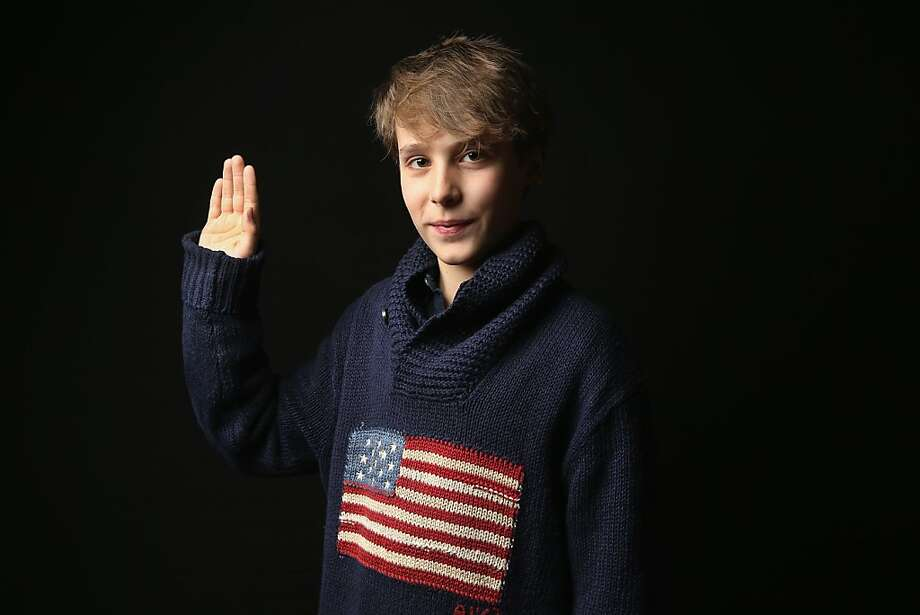Sixth grader Maximilian Poncer, 12, born in France, holds his hand as for the oath of allegiance while awaiting his American citizenship certificate at the U.S. Citizenship and Immigration Services (USCIS), office on February 19, 2013 in New York City. His mother is a marketing consultant, and the family lives in New York City. Photo: John Moore, Getty Images