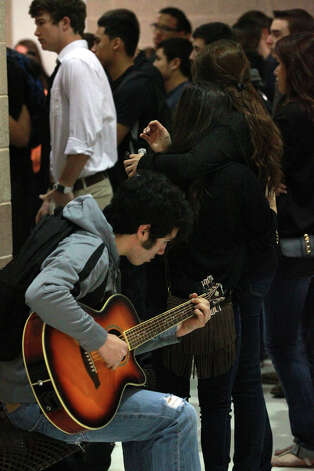 A Brandeis High School student plays guitar as two female students embrace behind him during a gathering at the school Wednesday February 20, 2013 the day after Brandeis High School student Gabriella Lerma was killed in a car crash. Photo: JOHN DAVENPORT, San Antonio Express-News / �San Antonio Express-News/Photo Can Be Sold to the Public
