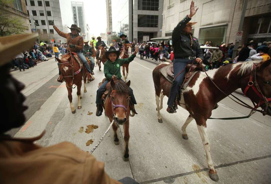 Sandra Price, Deona Horace, and Minnie Horace wave to spectators as they ride with the Southwest Trail Ride during the Houston Livestock Show and Rodeo Downtown Parade on Saturday, Feb. 25, 2012, in Houston. ( Mayra Beltran / Houston Chronicle ) Photo: Mayra Beltran, Staff / © 2012 Houston Chronicle