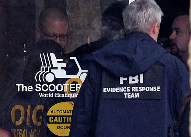 Agents stand in the doorway at building number 1 as FBI and OIG raid the Scooter Store in New Braunfels on February 20, 2013. Photo: TOM REEL, Tom Reel/Express-News