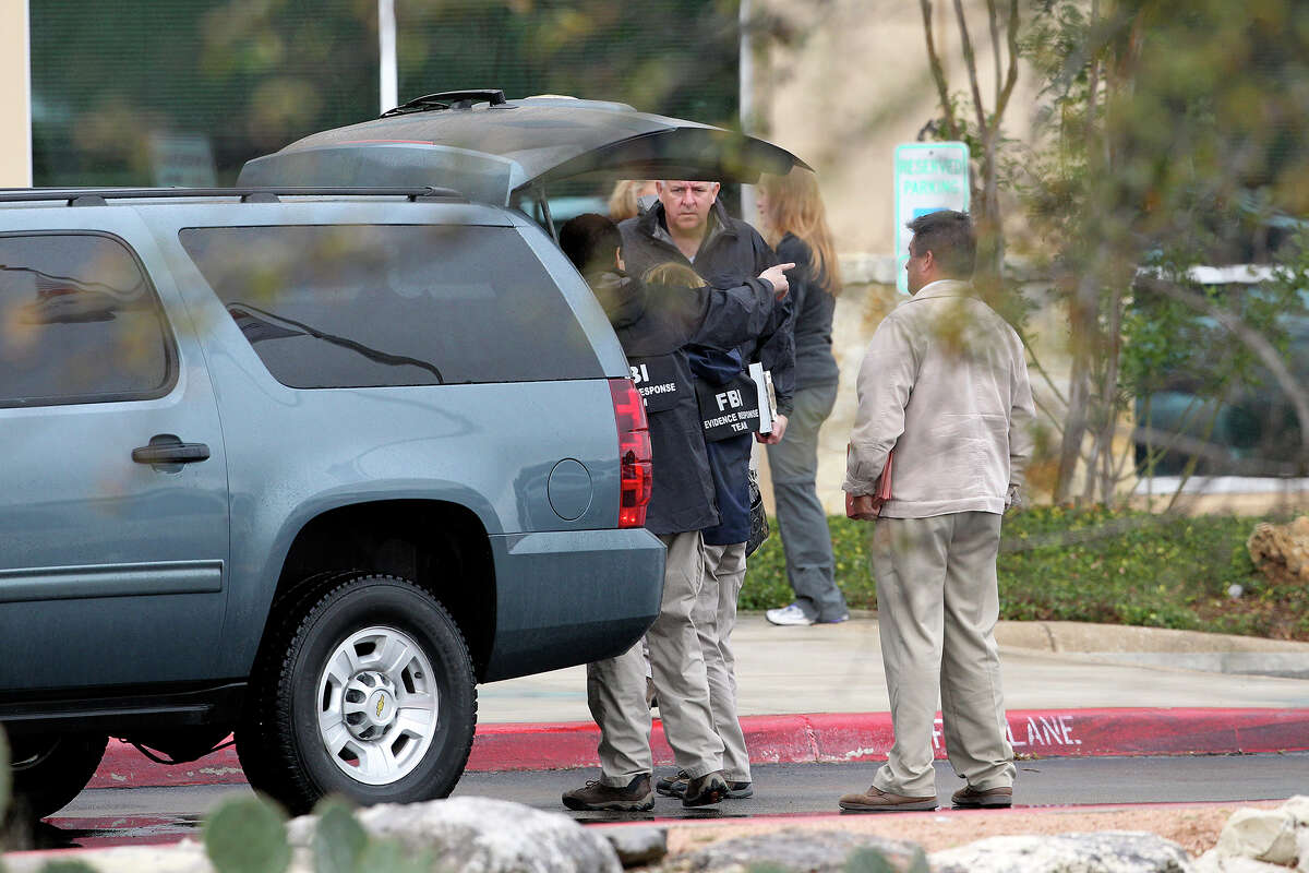 Agents stage from their vehicle in front of the building as FBI and OIG raid the Scooter Store in New Braunfels on February 20, 2013.