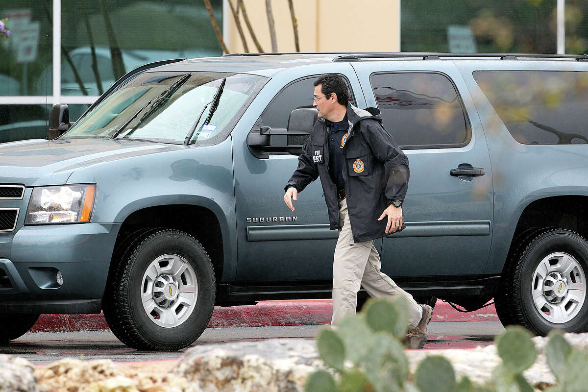 An FBI agent hrries into the front of the building after exiting his vehicle as FBI and OIG raid the Scooter Store in New Braunfels on February 20, 2013.