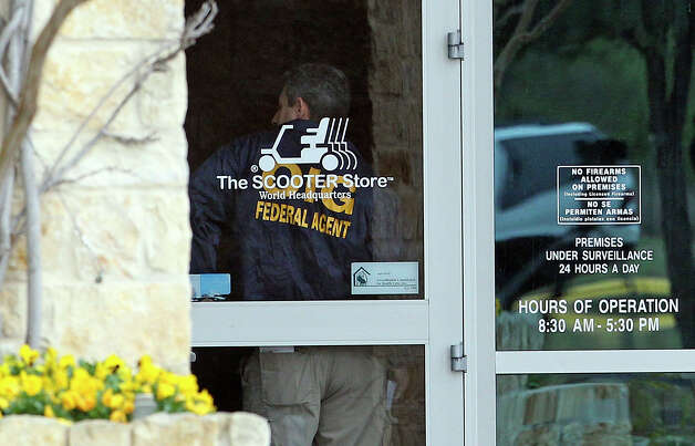 An agent stands at the front door of the building No. 1 as FBI and OIG search The Scooter Store in New Braunfels on Feb. 20, 2013. Photo: TOM REEL, San Antonio Express-News / San Antonio Express-News