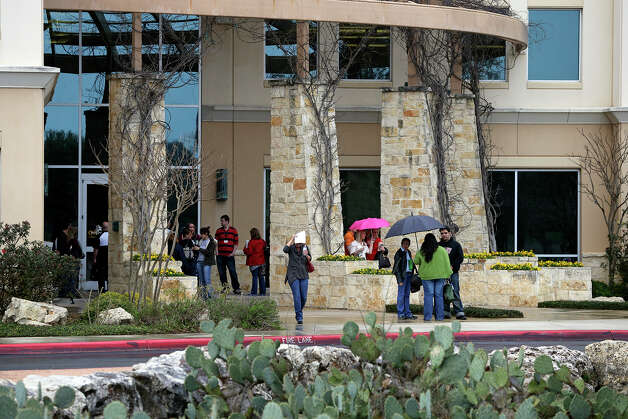 Employees leave in the rain as FBI and OIG search The Scooter Store in New Braunfels on Feb. 20, 2013. Photo: TOM REEL