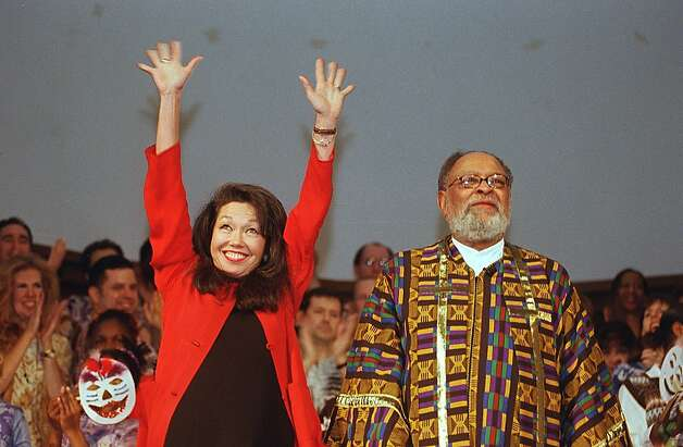 Janice Mirikitani raises her hands to celebrate not only her birthday but also the announcement of her appointment as the city's new poet laureate while her husband Reverand Cecil Williams stands by during Sunday services at Glide Memorial Church in 2000. Photo: Robin Weiner, SFC
