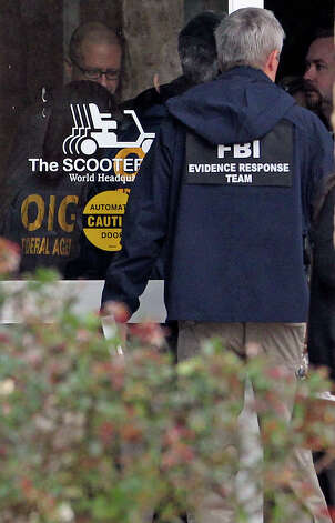 Agents cluster at the front door of building number 1 as FBI and OIG raid The Scooter Store in New Braunfels on Feb. 20, 2013. Photo: TOM REEL
