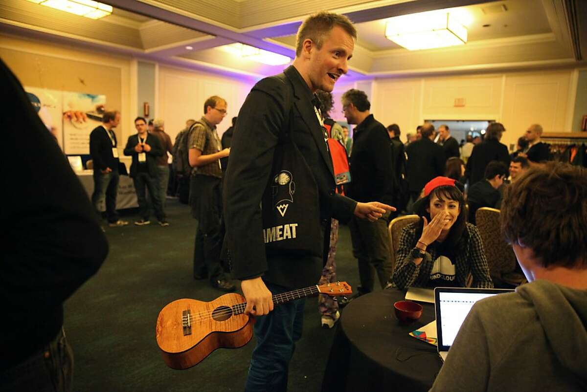 Joe Sumner (standing center), founder Vyclone, and Tegan Gaan, (at right with red hat), founder Gigit, discuss future work together in the Imperial Ballroom at the SF MusicTech Summit at Hotel Kabuki on Tuesday, February 19, 2013 in San Francisco, Calif.