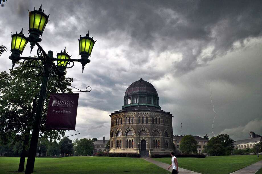 A bolt of lightning can be seen in the distance beyond the Nott Memorial at Union College during storms on Tuesday afternoon May 29, 2012 in Schenectady, NY.   (Philip Kamrass / Times Union ) Photo: Philip Kamrass / 00017861A