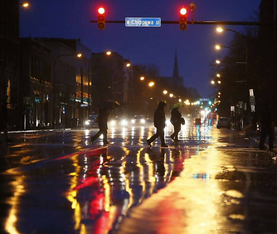 Night owls - or early risers - cross Delaware Avenue at Chippewa Street in Buffalo, N.Y., before sunrise on a rainy morning. Photo: Derek Gee, Associated Press