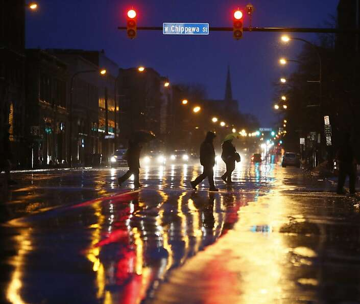 Night owls - or early risers - cross Delaware Avenue at Chippewa Street in Buffalo, N.Y., bef