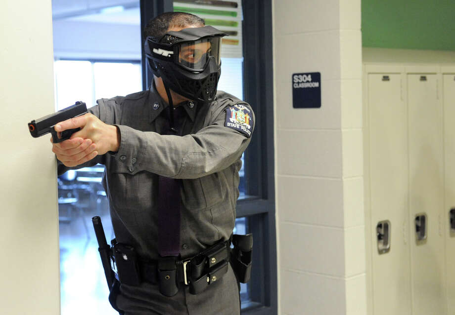 Police officers run drills in the hallways as the East Greenbush Police Department host an ?active shooter? training class at Columbia High School on Wednesday Feb. 20, 2013 in East Greenbush, N.Y. The purpose of this training is to prepare for an incident regarding a person(s) that is shooting inside a school, church, restaurant, mall or anyplace where large amounts of people are gathered.  (Lori Van Buren / Times Union) Photo: Lori Van Buren