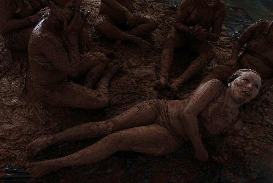 Women bathe in mud in a presentation for the inauguration of the National Meeting of Rural Women, in Brasilia, Brazil, Monday, Feb. 18, 2013. The four-day event aims to discuss the issues of violence against women and exploitation of women in rural areas. (AP Photo/Eraldo Peres) Photo: Eraldo Peres, Associated Press
