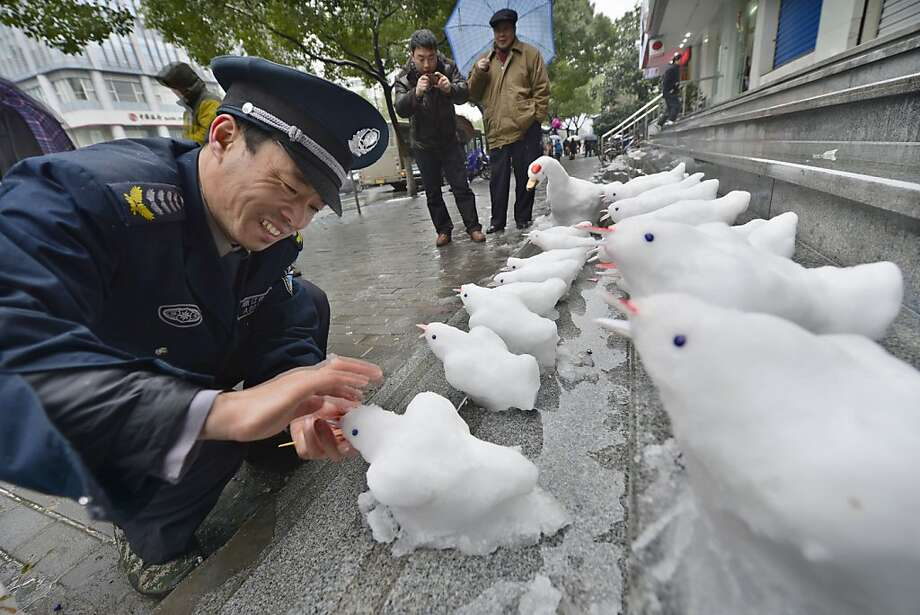 Tweeting on the job: As a security guard, Du Jinqian's job is to protect the bank where he works in Hangzhou, China, but his real love is sculpting little snow birds on the bank steps. Photo: ChinaFotoPress, Getty Images