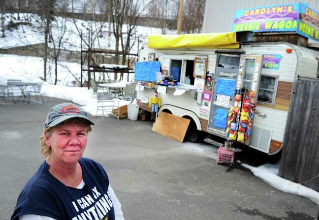 Carolyn Schumacher stands near CarolynâÄôs Weenie Wagon at its currect location between the site of the former Housatonic Wire Co. factory building on River Street and former Seymour Lumber Company on Bank Street in Seymour, Conn. Wednesday, Feb. 20, 2013. Schumacher will have to relocate her business because Seymour Lumber Company plans to sell the site and evict her. Photo: Autumn Driscoll / Connecticut Post