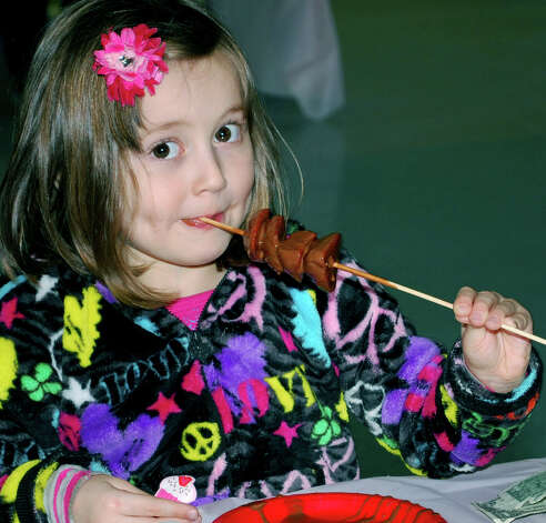 Jenna Anderson, 4, of Kent was surprised to have her photo taken while eating chocolate-covered strawberries on a stick during the 18th annual Chocolate Fest, hosted by the Kent Center School Scholarship Fund committee Feb. 6, 2013 at the school. Photo: Deborah Rose