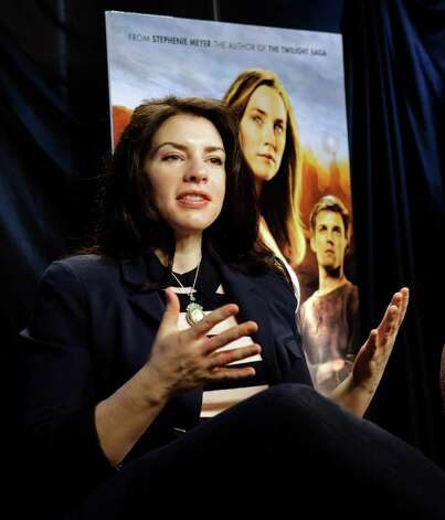 "This Feb. 19, 2013 photo shows author Stephenie Meyer speaking in Miami. Meyer, author of the ""Twilight"" saga says she's working on a new series.  She wrote ""The Host"" as an escape from editing of one of the books in the popular vampire series. The movie adaption of ""The Host"" premieres March 29. (AP Photo/Alan Diaz) Photo: Alan Diaz"