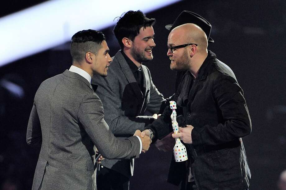 LONDON, ENGLAND - FEBRUARY 20:  Jonny Buckland and Will Champion of Coldplay receive the award for British Live Act from Louis Smith and Jack Whitehall on stage during the Brit Awards 2013 at the 02 Arena on February 20, 2013 in London, England.  (Photo by Matt Kent/Getty Images) Photo: Matt Kent, Getty Images