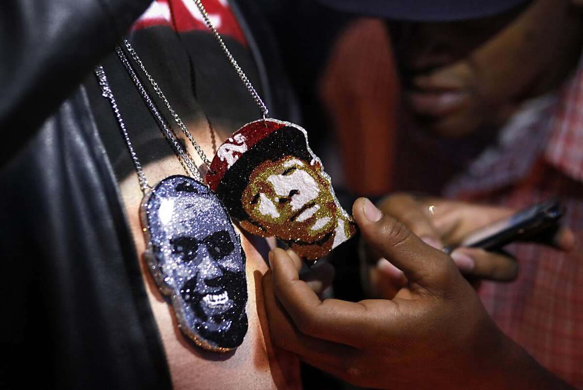 Saturday February 16, 2013, at a candlelight vigil marking the one year anniversary of the death of his son, Ramon Price Sr. displays the necklaces that he had made with the face of Lamont and the face Damian Williams, both who were killed on the streets of Oakland, Calif. Photo: Lacy Atkins, The Chronicle