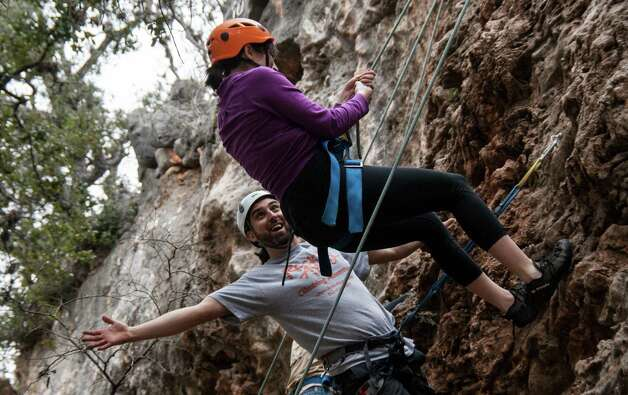 Rock-About guide Carlos Garza cheers on Esther Davis of Austin as she makes her way down the cliff face at Reimer's Ranch in Dripping Springs. Photo by Joshua Trudell//Special to the Express-News Photo: Josh Trudell, For The Express-News / © Copyright 2013 Josh Trudell Photography. All Rights Reserved.
