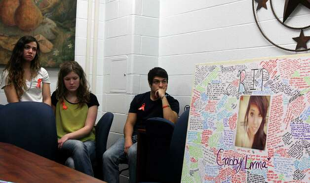 Brandeis High School students (from left to right) Paola Lewis, 17, Courtney Devore, 16, and Joseph Camarano, 17, listen while Northside Independent School District officials speak to the media on Feb. 20, 2012, about the fatal car crash that took place Tuesday involving students from the school. The poster on the right was signed by students in memory of Gabriella Lerma, 17, who was killed in the accident. Photo: JOHN DAVENPORT, San Antonio Express-News / ©San Antonio Express-News/Photo Can Be Sold to the Public