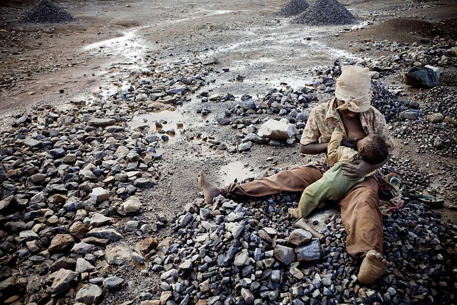 A female miner takes a break from her hard work to breast feeds her child. Photo: Gwenn Dubourthoumieu