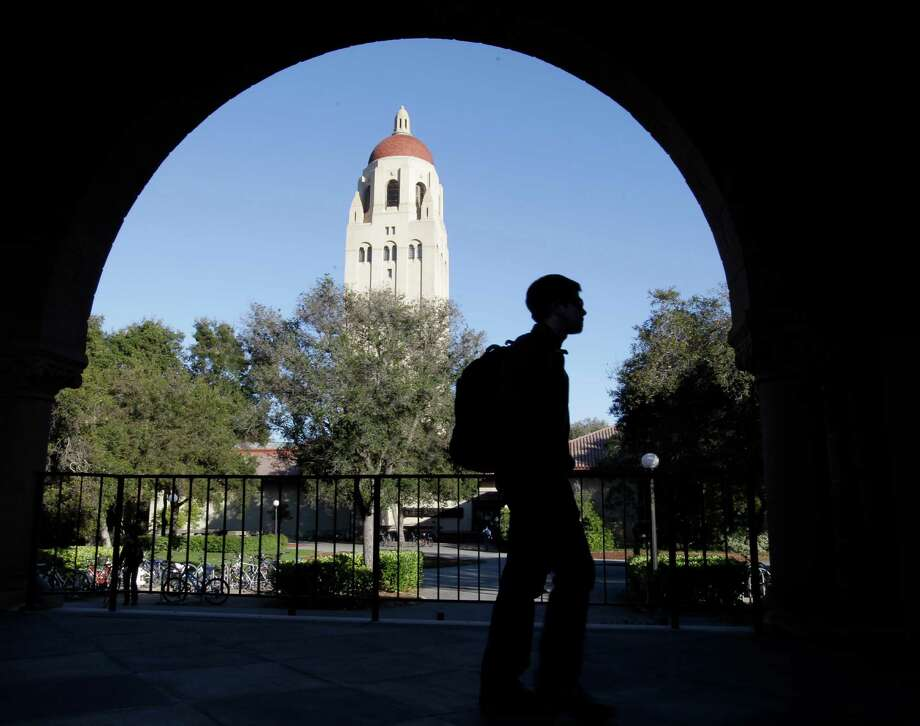 FILE - In this Feb. 15, 2012 file photo, a Stanford University student walks in front of Hoover Tower on the Stanford University campus in Palo Alto, Calif.  Stanford University became the first school to raise $1 billion in a single year, according to an annual college fundraising report released Wednesday, Feb. 20, 2013 that shows that elite institutions continue to grab a disproportionate share of donor dollars. (AP Photo/Paul Sakuma, File) Photo: Paul Sakuma