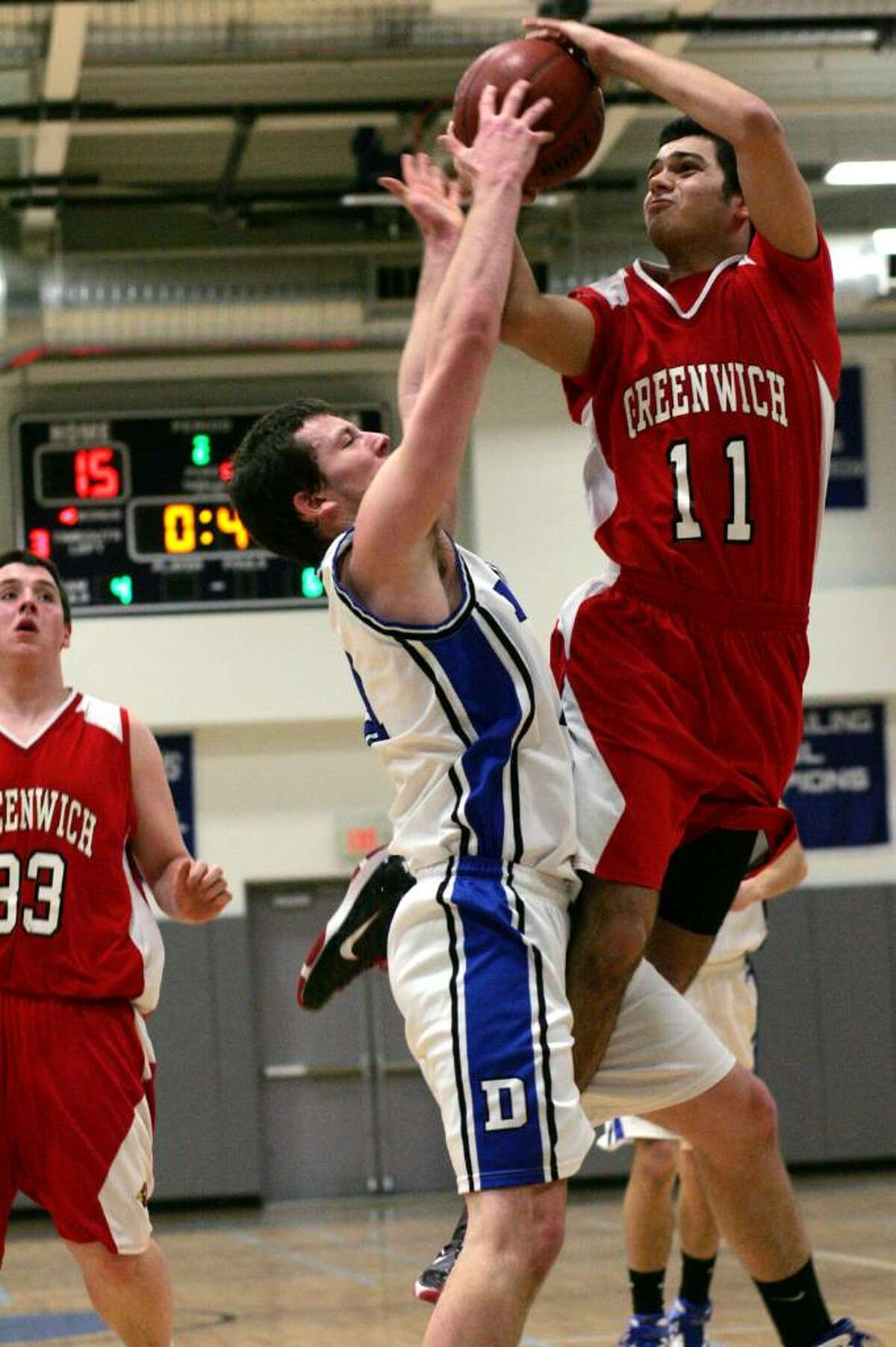 Greenwich High School's Brian Leeds works hard to the basket against Darien's Wes Blummer during Wednesday evenings championship game of the La Vista Tournament held annually at Darien High School.