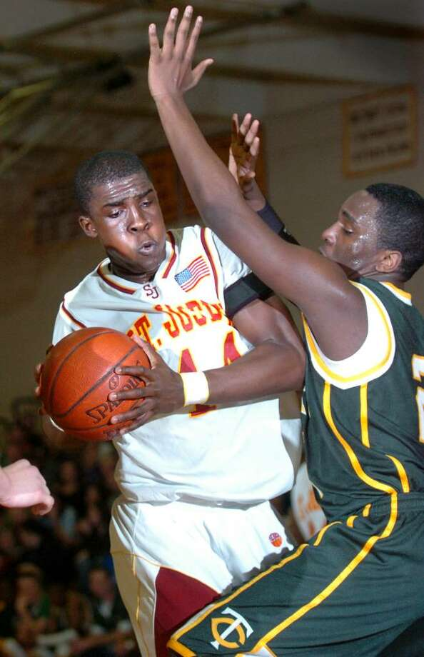 St. Joseph's Oscar Assie controls the ball as Trinity Catholic's Aaron Spence guards him during the second half of Wednesday night's NECC tournament championship game in Trumbull. Photo: Autumn Driscoll / Connecticut Post