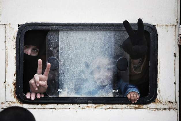 Displaced Syrian people make the victory sign inside wagon while going to Azaz camp for displaced people, north of Aleppo province, Syria, Wednesday, Feb. 20, 2013. According to Syrian activists the number of people in the Azaz camp has grown by 3,000 in the last weeks due to heavier shelling by government forces. (AP Photo/Manu Brabo) Photo: Manu Brabo, Associated Press
