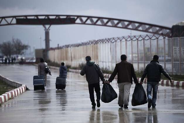 Displaced Syrian people bring basics from Turkey into Syria at the border between the two countries, north of Aleppo province, Syria, Wednesday, Feb. 20, 2013. (AP Photo/Manu Brabo) Photo: Manu Brabo, Associated Press