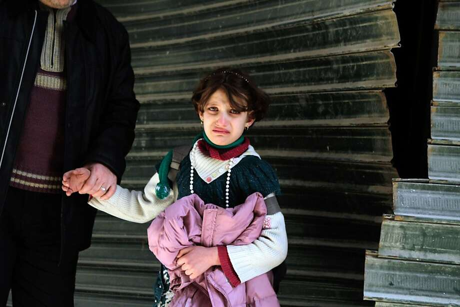 A distraught Syrian girl is consoled after an explosion in Aleppo. The nearly 2-year-old conflict has reportedly killed more than 70,000 people. Photo: Mauricio Morales, AFP/Getty Images