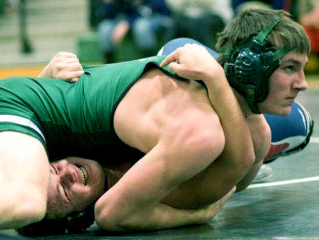 The Green Wave's Thomas McILveen cooly checks with coach Chris Piel for guidance as he delivers a clutch pin at 195 pounds over the Rebels' L.J. Quarato to clinch as New Milford HIgh School wrestling's 47-26 triumph over  New Fairfield, Feb. 6, 2013 at NMHS. Photo: Contributed Photo