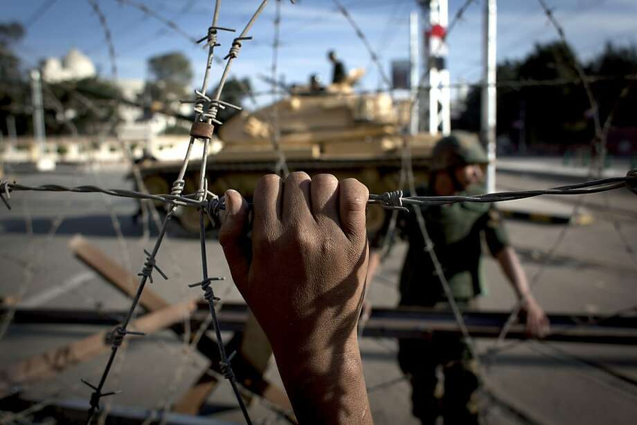 FILE - In this Thursday, Dec. 6, 2012 file photo, an Egyptian army tank is seen behind barbed wire securing the perimeter of the presidential palace while protesters on the other side chant anti President Mohammed Morsi slogans, in Cairo, Egypt. Egypt's powerful military is showing signs of growing impatience with the country's Islamist leaders, criticizing their policies and issuing thinly-veiled threats that it might seize power again. The tension is raising the specter of another military intervention in politics much like the one in 2011, when generals ousted longtime authoritarian leader Hosni Mubarak to end the 18-day popular uprising. (AP Photo/Nasser Nasser, File) Photo: Nasser Nasser, Associated Press